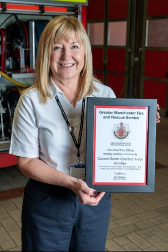 Tracy Brindley holding the commendation she was awarded