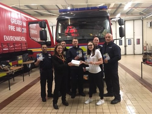 Firefighters present the iPad to the 2019 Glovebox guide winner